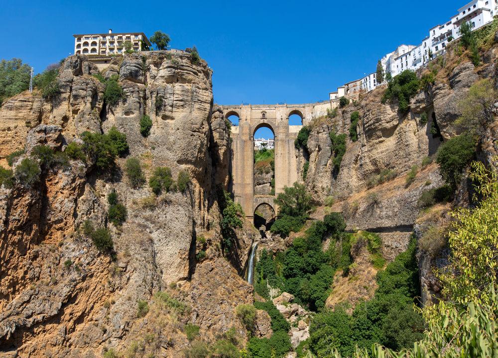 Den vita staden Ronda ligger dramatiskt på en klippa. Broarna över  bergsklyftan El Tajo, Spaniens äldsta tjurfäktningsarena och lämningar efter både romare och morer är några av stadens sevärdheter.